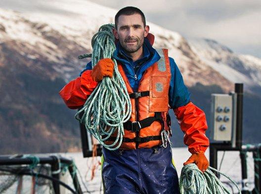 Fisker med redningsvest og tauverk over skuldra på oppdrettsanlegg