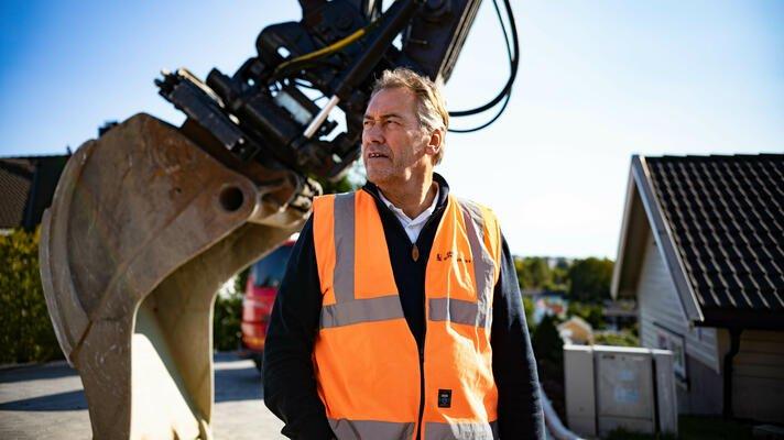 Terje Andersen, administrerende direktør i Råde Graveservice, ute på en byggeplass med gravemaskin i bakgrunnen.