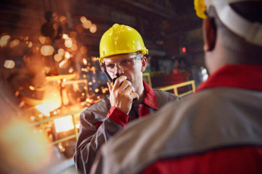 Industriarbeider  i gul hjelm som snakker i walkie-talkie