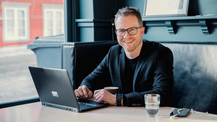 Andreas Østenrød, administrerende direktør i Ressurs Tromsø, i en sofa med en laptop på bordet.