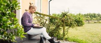 Dame som sitter på trappen utenfor huset sitt og ser på en PC-skjerm.