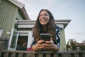 Dame med mobil på terassen