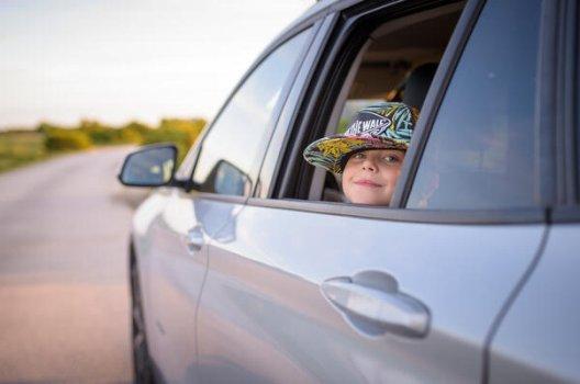liten jente med hatt i bilvindu