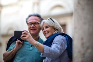 Et eldre par som ser på en mobil