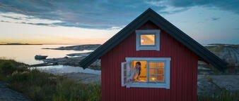 Illustrasjonsfoto: ung kvinne lukker hyttevinduet