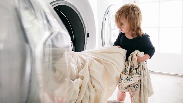 Illustrasjonsfoto: barn legger tøy i vaskemaskinen.