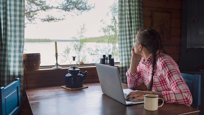 Dame med rødrutete skjorte som sitter ved et spisebord på en hytte og ser ut vinduet.