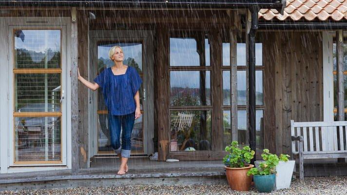 Dame med blå bluse som står utenfor huset sitt og ser på regnet som pøser ned.