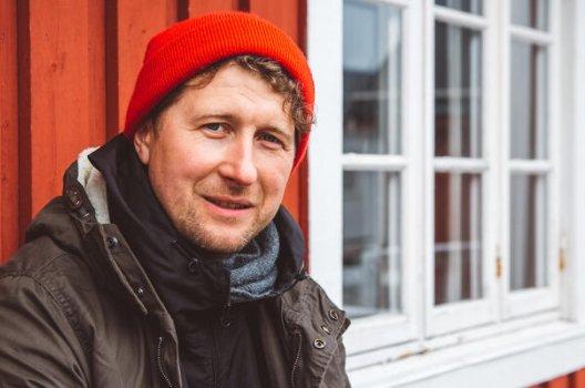 Mann med rød lue sitter ved hytteveggen