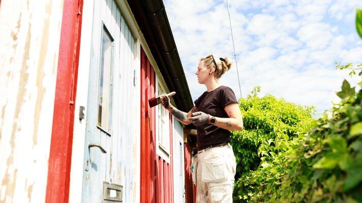 Dame som maler hytte rød å sommeren.