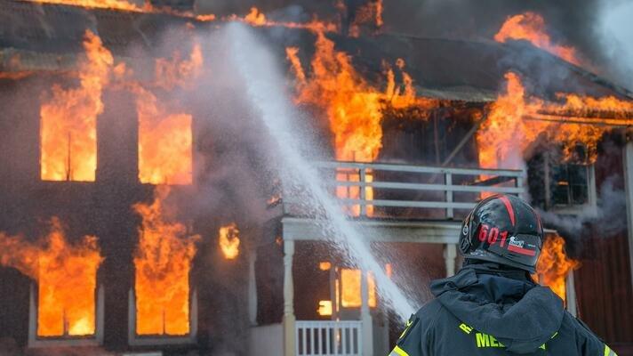 Hus som brenner og en brannmann som prøver å slukke det.