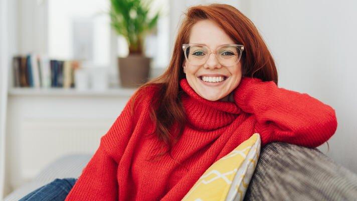 Dame med rød genser som sitter i en sofa.