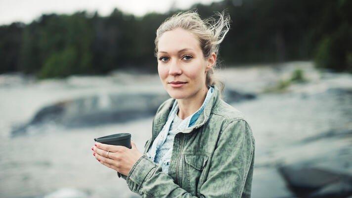 Illustrasjonsfoto: ung kvinne på tur med kaffekoppen i hånden.