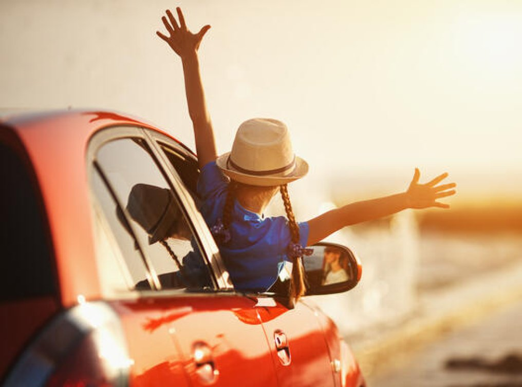 Illustrasjonsfoto: glad jente på biltur.