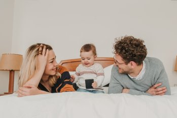 To voksne og ett barn ligger i en stor seng