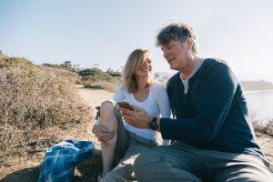 Kvinne og mann ser på mobil på sandstrand
