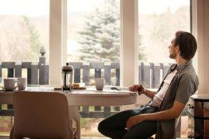 Ung mann ved frokostbord, ser ut av vinduet