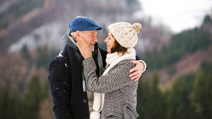 Eldre mann og kvinne holder rundt hverandre og det er fjell i bakgrunnen