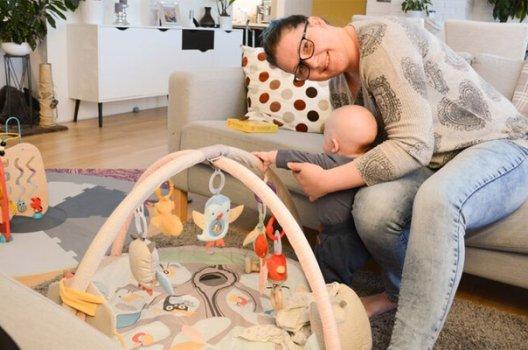 Ung kvinne og baby leker i babygym