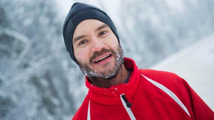 Portrett av mann med lue og snø i skjegget og rød skijakke