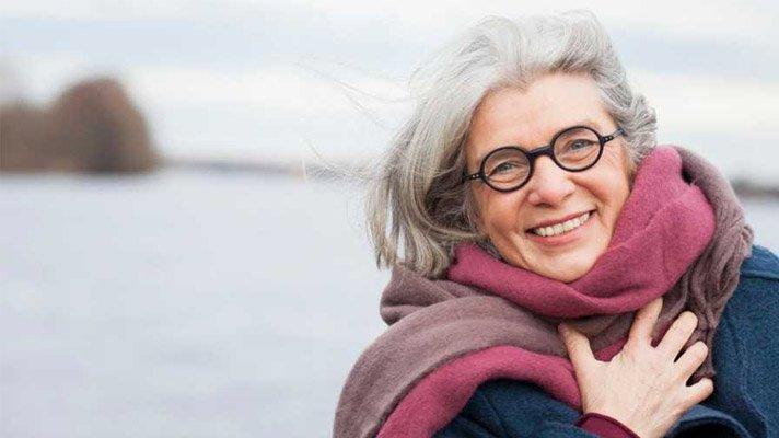 Smilende dame med runde briller og stort lilla skjef