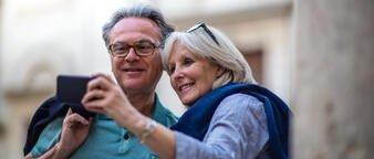 Pensjonistpar på ferie som ser på en mobil.