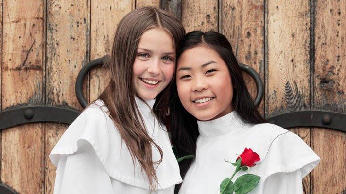 To smilende jenter i hvit konfirmasjonskjole