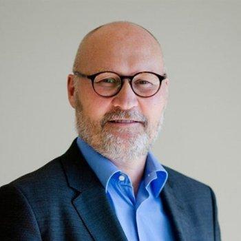 Mann i dress, med kort skjegg og runde briller