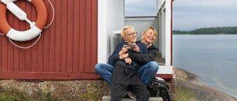 Mor og sønn sitter utenfor en hytte ved sjøen.