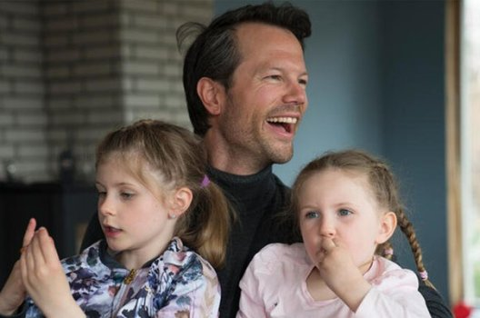 Ung mann som ler, sammen med to små jenter