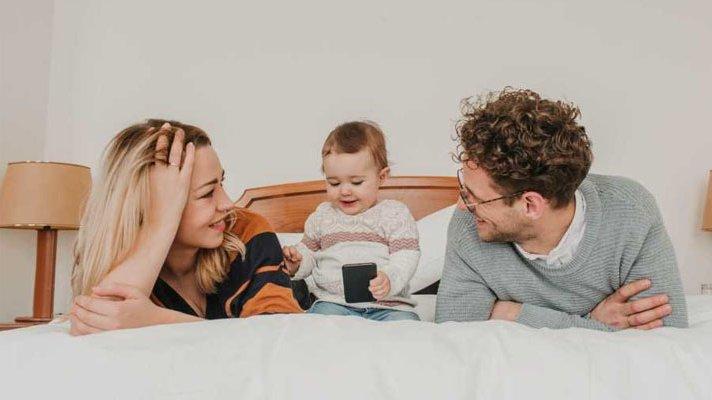 Kvinne og mann som ligger på en seng, med et barn som ser på en mobil i midten