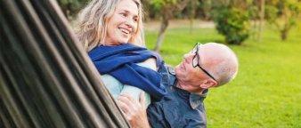Eldre par som sitter sammen i en hengekøye