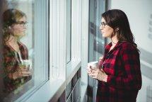 En dame ser ut av vinduet betenktsomt.