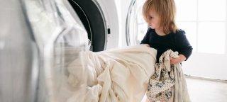 Et barn som tar ut klær fra en vaskemaskin.
