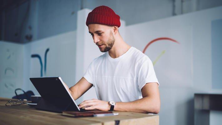 Mann med rød lue som sitter ved en PC.