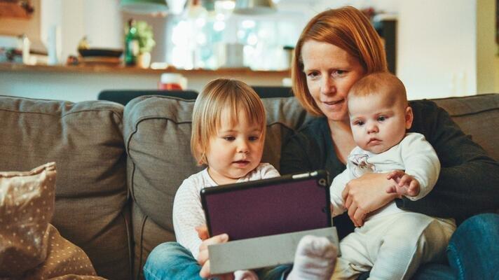 Mor med to barn hjemme i sofaen som ser på et nettbrett.