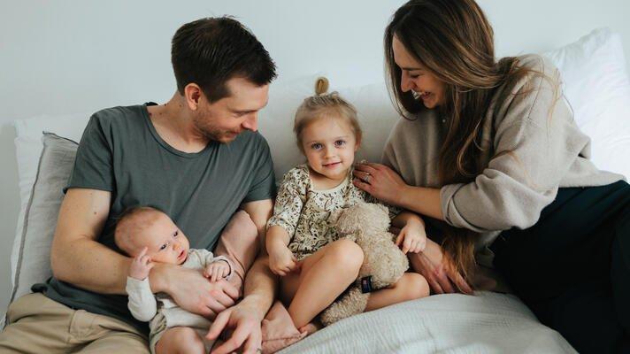 En familie med to barn som sitter i en seng.