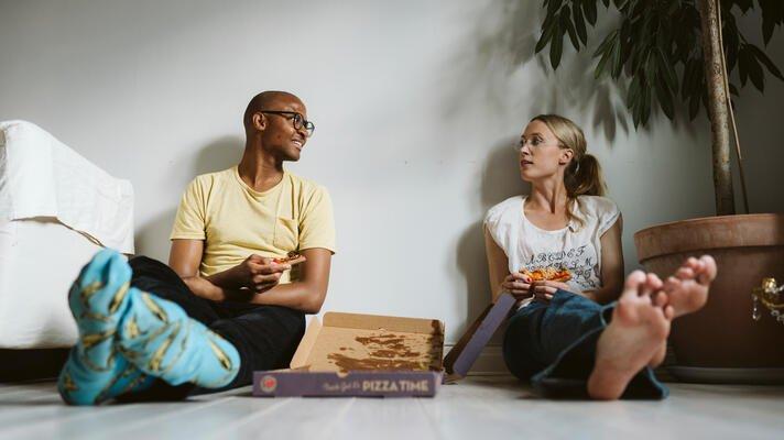 Ungt par som sitter på gulvet og spiser pizza.