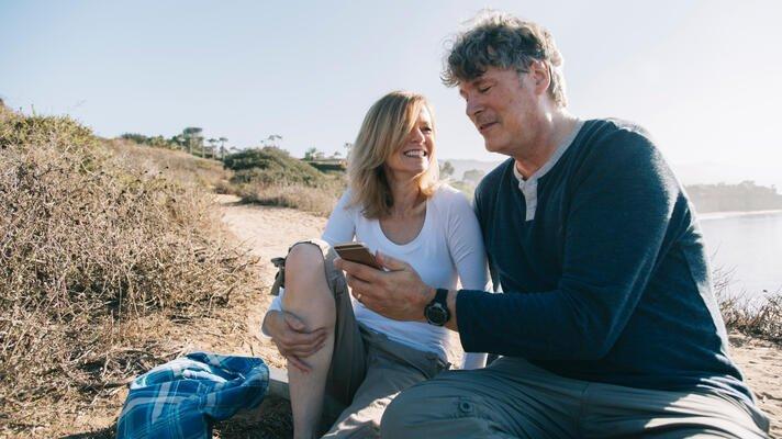 Smilende eldre par som sjekker mobilen på stranda.