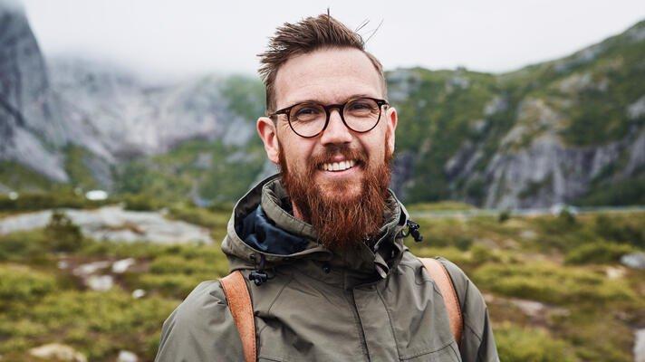 Portrettfoto av ung mann på tur i naturen med rødt skjegg, briller og skinnryggsekk.