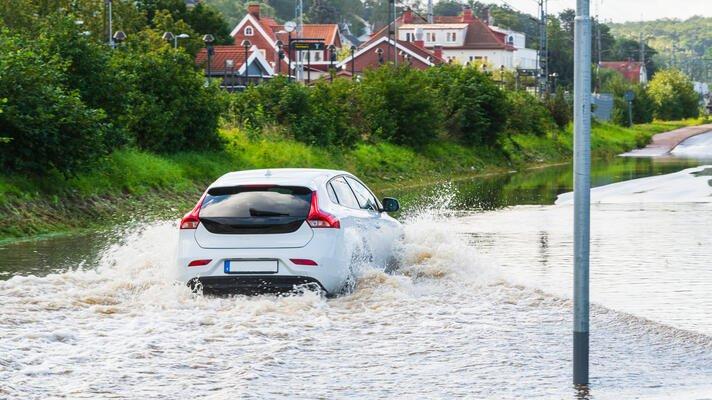 Bil som kjører gjennom flommen.