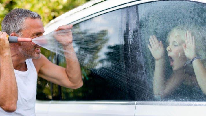 Far med grått hår og skjegg vasker bilvinduet med artig unge som presser nesen opp mot vinduet på andre siden.