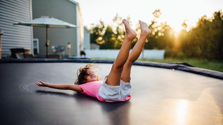 Barn i t-skjorte som lander på rygg på en trampoline. I solnedgang.