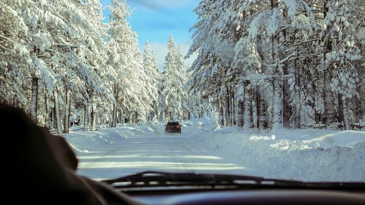 Vinterbilde tatt fra innsiden av en bil. Snødekt vei med bil foran.