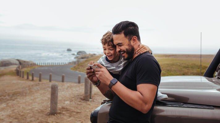 Ung far og hans sønn som titter på en mobil og ler godt. Lener seg på brun bil, ved en strandvei.