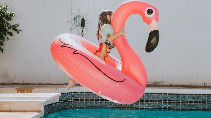 Jente hopper i badebasseng om sommeren.