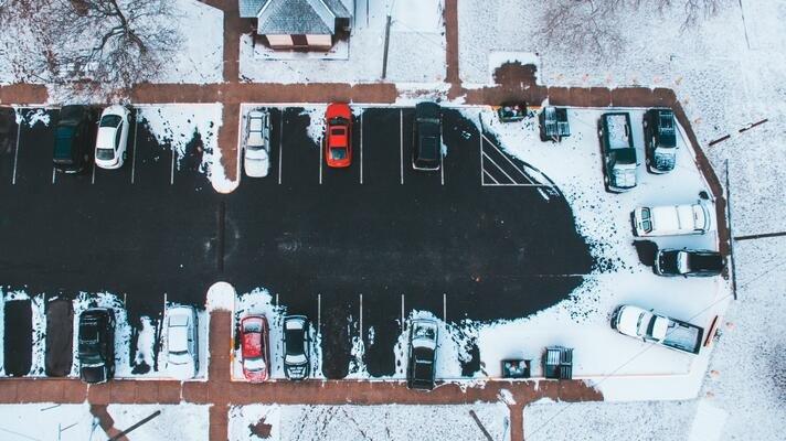 Biler på parkeringsplass om vinteren.