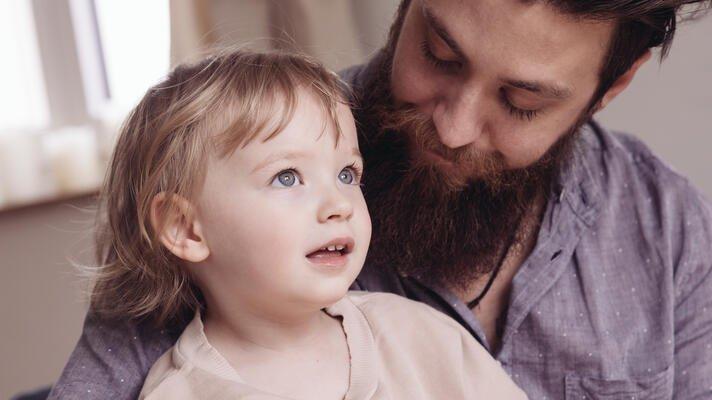 Illustrasjonsfoto: mann og barn sitter inne.