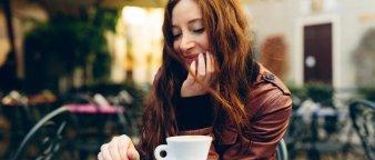 Dame på kafé som drikker kaffe og sjekker mobilen.