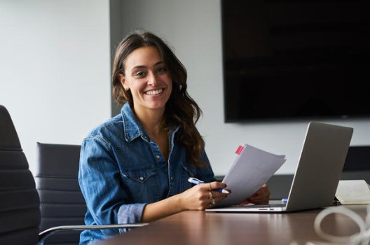 Kvinne sitter ved at bord og holder pen og papir